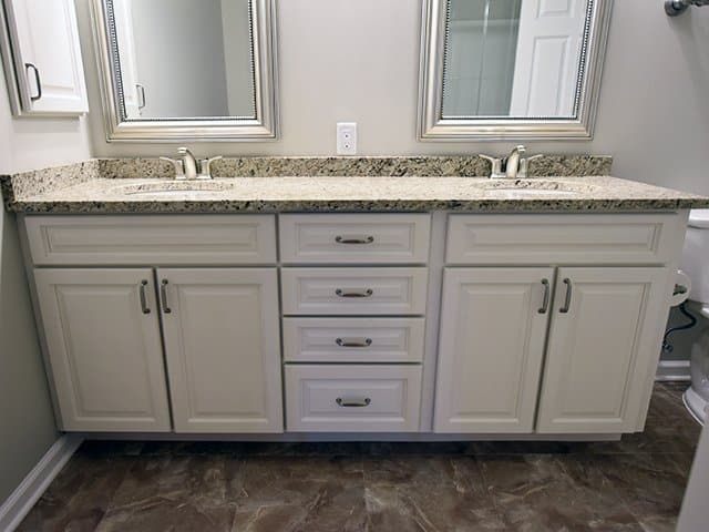 an off-white double vanity with granite countertop in a Linden Ponds apartment in Hingham, MA