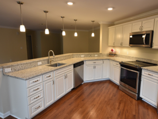 an off-white kitchen with angled peninsula and granite countertops inside of a Linden Ponds apartment in Hingham, MA