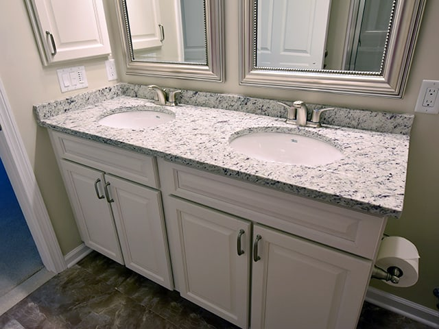 double bath vanity with off white cabinets and granite countertop in a Linden Ponds apartment in Hingham, MA