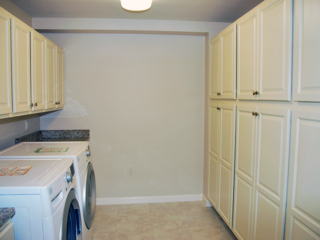 laundry room with off-white utility cabinets and a white front-loading washer and dryer in a Linden Ponds apartment in Hingham, MA