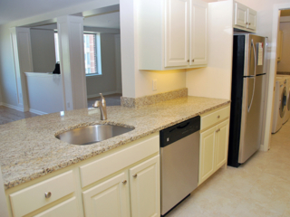 off white cabinets and a brown speckled granite countertop with a stainless steel sink, dishwasher and refrigerator in a Linden Ponds apartment in Hingham, MA