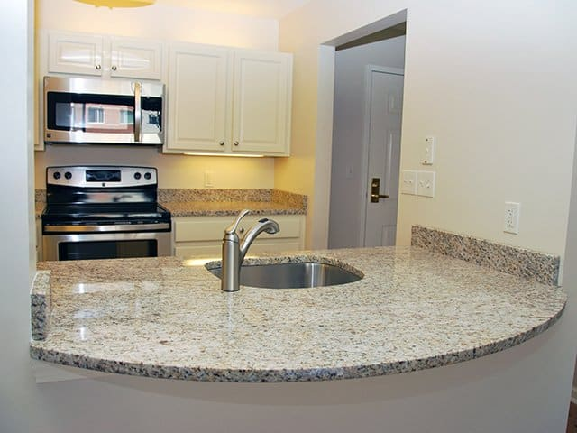 close up of an off-white kitchen with granite countertops in a Linden Ponds apartment home in Hingham, MA