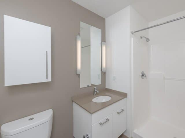 a modern white single bath vanity with quartz vanity top in an Ames Shovel Works apartment in North Easton, MA