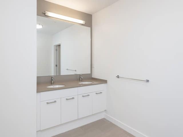 a modern white double bath vanity with quartz vanity top in an Ames Shovel Works apartment in North Easton, MA