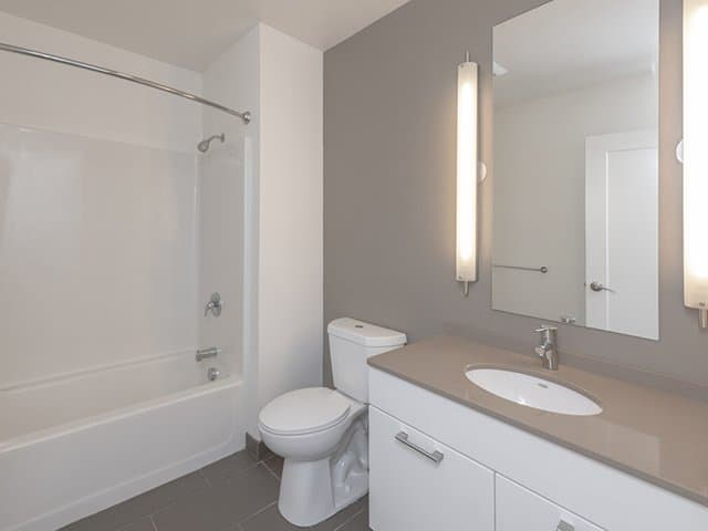a modern white single bath vanity with quartz vanity top, a white toilet and tub/shower in an Ames Shovel Works apartment in North Easton, MA