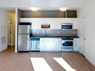 modern white kitchen cabinets with quartz countertops and stainless steel kitchen appliances in an Ames Shovel Works apartment in North Easton, MA