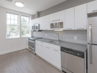 modern white kitchen cabinets with quartz countertops and stainless steel appliances in an Ames Shovel Works apartment in North Easton, MA