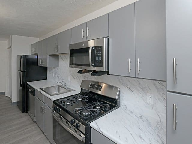 a grey kitchen inside a Braintree Village apartment in Braintree, MA