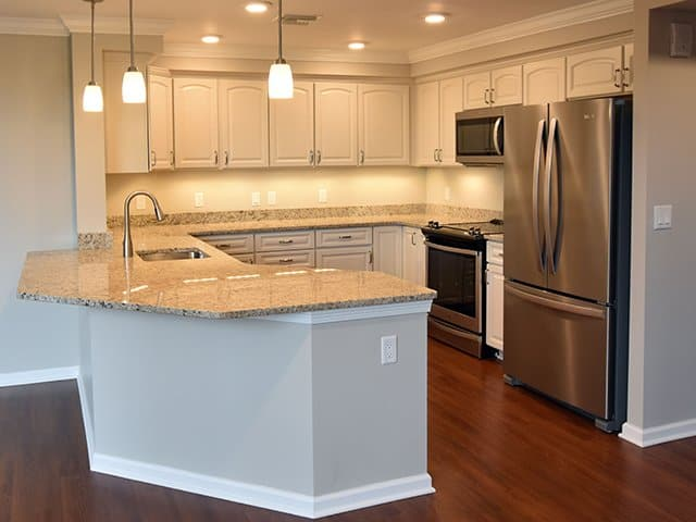 an off-white kitchen with large peninsula and granite countertops inside of a Linden Ponds apartment in Hingham, MA