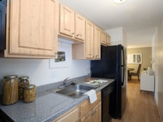 kitchen cabinets in a honey finish with a laminate countertop and black kitchen appliances in a Northgate apartment home in Revere, MA