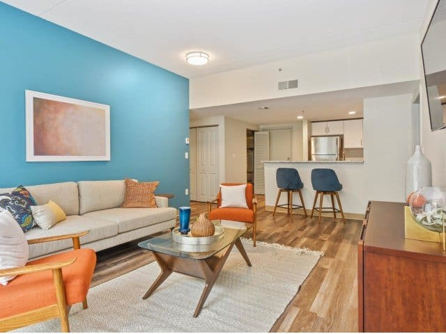 a living area and kitchen inside of a Strata apartment in Malden, MA