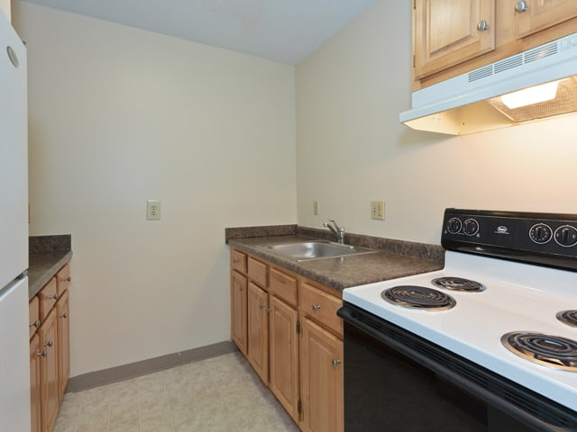 affordable housing kitchen with extreme use honey-finish wood cabinets and a black and white stove in a Market Mill apartment in Lowell, MA
