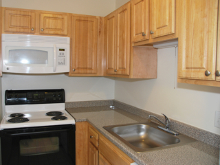 raised panel kitchen cabinets and a laminate countertop with a white, over the stove microwave and black and white electric stove in a Northgate apartment home in Revere, MA