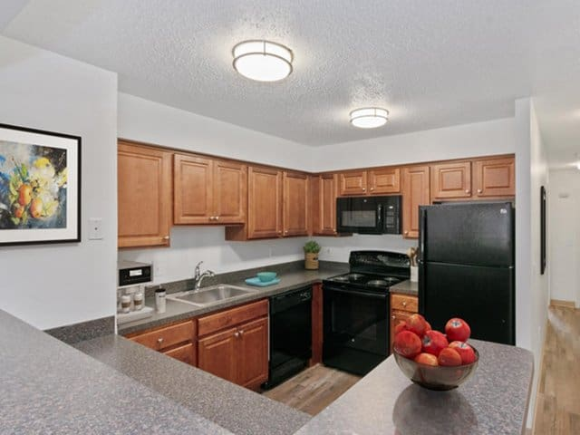 a kitchen in Stockbridge Court Apartments featuring medium-finish stained cabinets, laminate countertops and black appliances in Springfield, MA