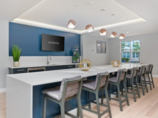 a community space with cabinets, countertops, stools and a TV at Strata apartments in Malden, MA