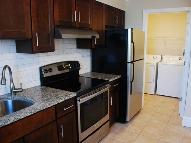 an autumn brown kitchen with laminate countertops and stainless steel appliances, with a doorway leading to a laundry area, in a Weymouth Commons apartment in Weymouth, MA