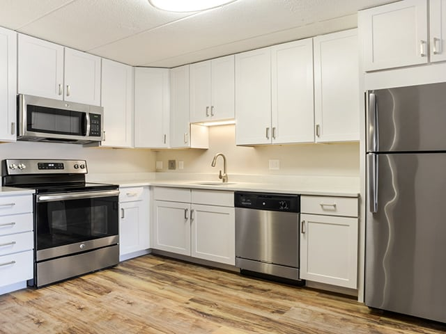 white L-shaped kitchen with stainless steel appliances